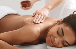 Beauty procedures at spa. Masseuse applying body scrub on black girl back, closeup