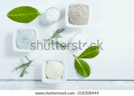 beauty products, cosmetic clay powder, bath salt and cream on white wooden table background