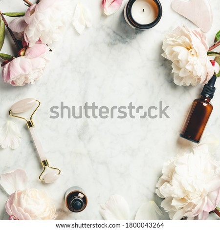 Beauty Products. Facial Roller, essential oils, towel and beautiful peonies on white marble background. Flat lay, top view. Massage tool for facial skin care, SPA beauty treatment concept