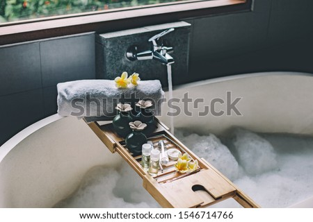 Beauty products on tray on bathtub. Bath with foam is filling with water. Relaxing in Bali luxury spa hotel. Foto d'archivio ©