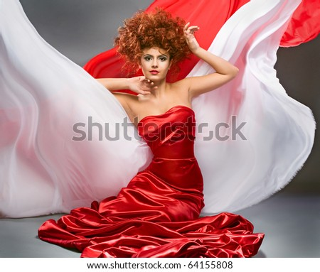 beauty redheaded girl in fashion dress on gray background