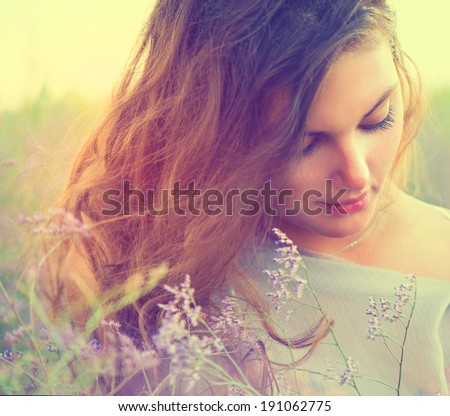 Beauty Romantic Girl Portrait. Sensual Woman Lying on a Meadow with Violet Flowers. Beautiful Woman Enjoying Nature. Romantic beauty in fantasy lavender field