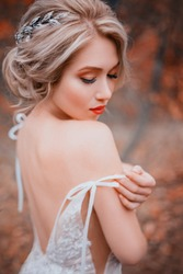 Beauty romantic young woman in white dress with open back gentle posing. silver diadem on blonde hair. Beautiful happy cute bride model girl enjoying nature outdoors. Delicate makeup in warm colors.
