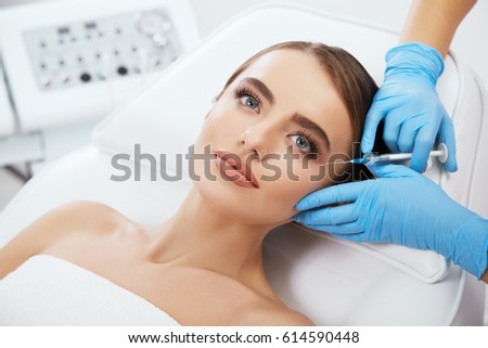 Shutterstock Beauty salon, doctor's hands in blue gloves holding syrringe with filler near girl's eyes. Contouring plastic surgery, head and shoulders of beautiful woman with blue eyes, closeup