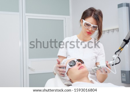 beauty salon girl worker carries out hair removal using latest generation appliance equipped with cooling system