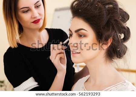 beauty salon, the girl dklayut makeup and styling in the salon, hairdressers and make-up artist, Concept for personal care and beauty #562193293