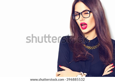 Stock Photo Beauty sexy fashion model business woman portrait, wearing glasses, isolated on white background. Beautiful young brunette girl with trendy accessories posing in studio. Perfect make-up. Girl winks