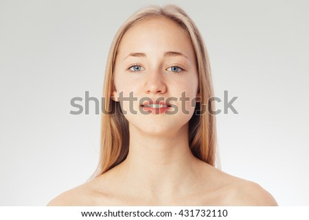 Beauty shoot of a young pretty girl nude. Blue eyes, blond hair, wearing no make-up in her perfect clear skin. Cosmetic advertisement style. Natural scandinavian face of a woman looking a t camera