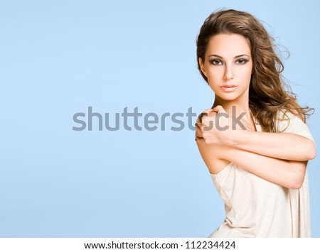 Beauty shot of a young brunette beauty on wide blue banner.