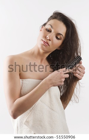 beauty shot of a young girl with a white bathrobe brushing her long wet hair