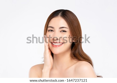 Beauty shot of smiling Asian woman model with clear fair skin doing hand touching face pose in white isolated background for skincare concept 商業照片 ©