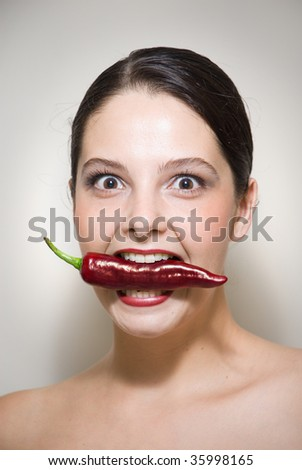 Beauty shot of woman holding red chili with teeth and red lips with eyes wide open