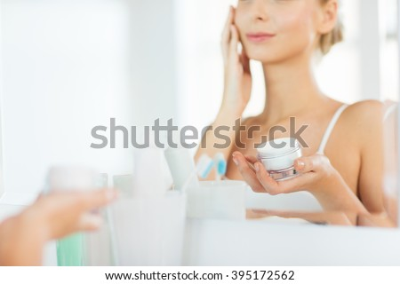 beauty, skin care and people concept - close up of smiling young woman applying cream to face mirror reflection at home bathroom