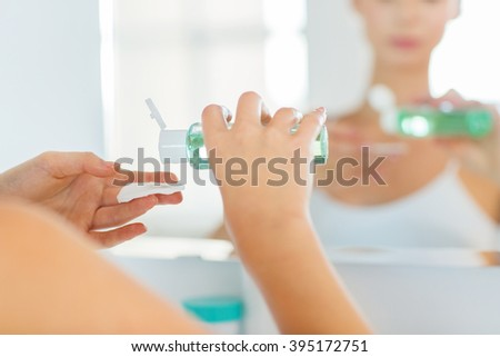 beauty, skin care and people concept - close up of young woman applying lotion to cotton disc for washing her face at bathroom