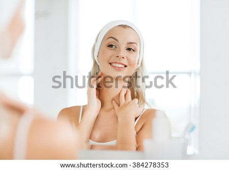 beauty, skin care and people concept - smiling young woman in hairband touching her face and looking to mirror at home bathroom #384278353