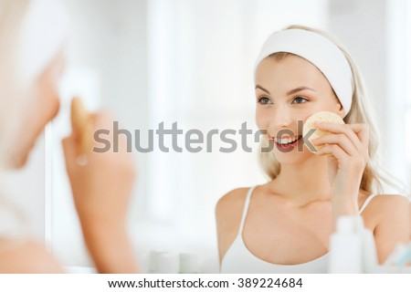 beauty, skin care and people concept - smiling young woman washing her face with facial cleansing sponge at bathroom #389224684