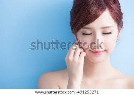 beauty skin care concept. woman relaxes. closed eyes. isolated on blue background, asian