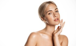 Beauty skin. Head and shoulders of blond woman model, touching glowing, hydrated facial skin, apply toner, skin cream or lotion for healthy look, after shower portrait, white background.