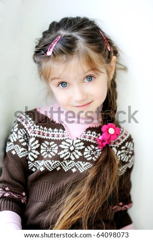 Beauty small girl with long dark braid and big blue eyes in winter sweater