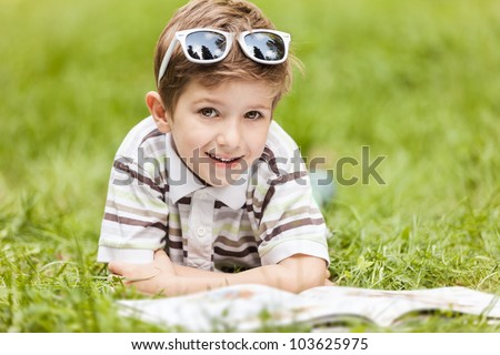 Beauty smiling child boy in sunglasses reading book outdoor on green grass field