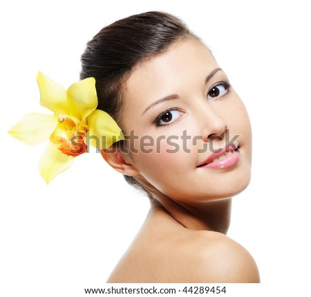 Beauty smiling female face with yellow orchid from her ear - over white background