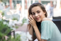 Beauty smiling happy model with natural make up and long eyelashes smiles in cafe. Copyspace. Young pretty student woman sitting outdoor.