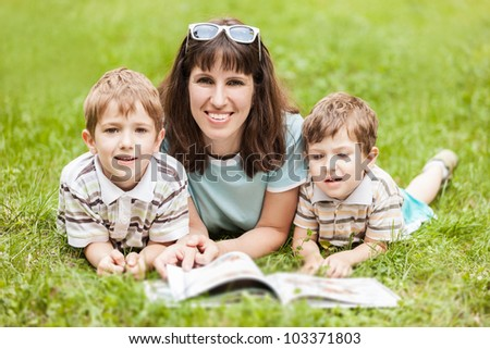 Beauty smiling mother and little sons reading book outdoor on green grass field