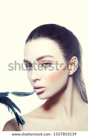 Beauty, spa. Attractive woman with beautiful face. Beautiful girl with daily makeup, youth and skin care concept. Touching perfect skin mouth lips with feather #1507803539