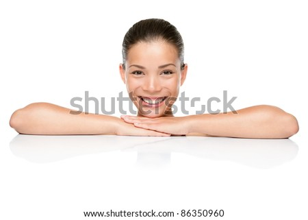 Beauty. Spa skin care woman smiling happy leaning face and arms on white blank copy space or edge. Beautiful mixed race Asian Caucasian female model isolated on white background.