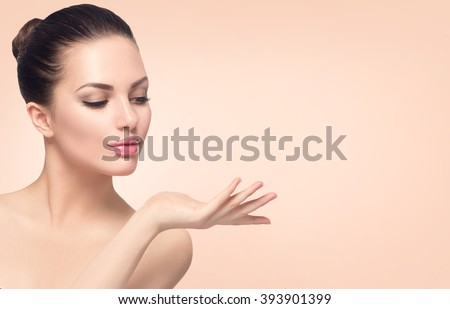 Beauty Spa Woman with perfect skin Portrait. Beautiful Brunette Spa Girl showing empty copy space on the open hand palm for text. Proposing a product. Gestures for advertisement. Beige background