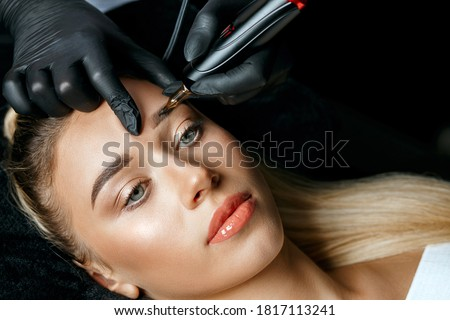 Beauty specialist hand doing eyebrow tattooing on a female brows Foto stock ©