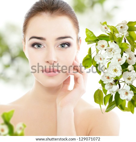 beauty spring girl portrait over blooming tree with flowers, young beautiful woman with clean skin holding hand near face