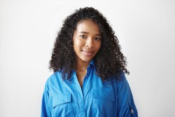 Beauty, style, people and fashion concept. Portrait of adorable charming young African American woman wearing stylish blue shirt expressing positive emotions, looking at camera with cute smile