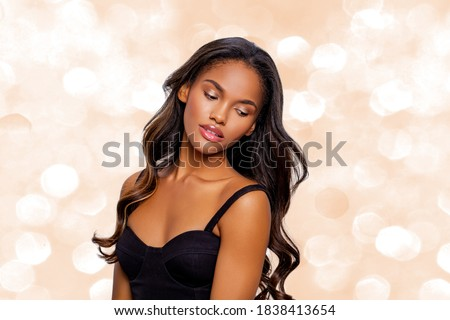 Beauty styled portrait of a young African - American woman. Fashion African - American girl with curly hair posing in the studio on a beige bokeh background. isolated. Studio shot.