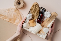 Beauty subscription Box preparation. Female hands holding gift box with natural skincare products, body brush, shampoo, soap, moisturizer.