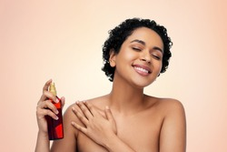 beauty, sun protection and bodycare concept - portrait of happy smiling young african american woman sunscreen oil spray in bottle over beige background