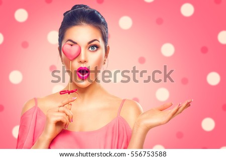 Beauty surprised Young fashion model Girl with Valentine Heart shaped cookie in hand. Love. Beautiful young woman pointing hand, advertising gesture. Valentines Day gift. Pink polka dots background.