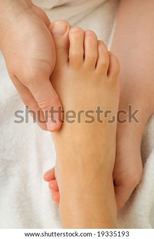 Beauty therapist hands massaging foot or pedicure
