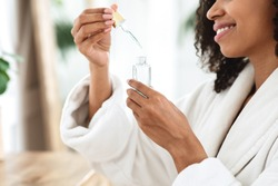 Beauty Treatment At Home. Smiling African Woman Opening Bottle With Moisturising Serum, Applying Product On Skin With Pipette, Side View
