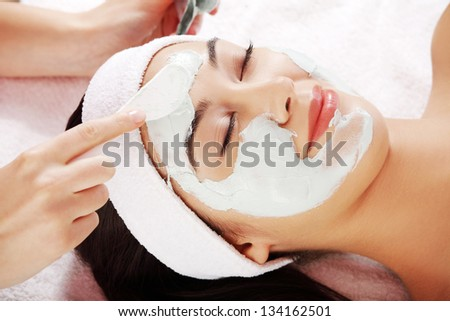 Beauty treatment in spa salon. Woman with facial clay mask.