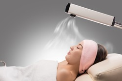 Beauty treatment of face skin with ozone facial steamer in spa center , asian women facing the steam. Steam for smooth skin