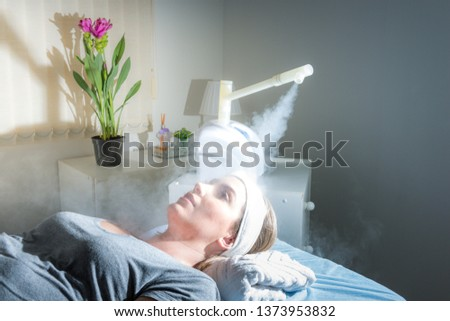 Beauty treatment of face with ozone facial steamer in beauty center. Beaultiful Blonde Girl. #1373953832