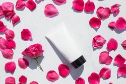 Beauty treatment. Tubes with pink roses on a white marble background. Beauty Spas and Wellness, anti-aging treatments with rose petals. The concept of purity, tenderness, freshness, youth.