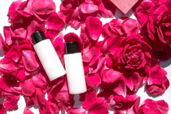 Beauty treatment. Tubes with pink roses on a white marble background. Beauty Spas and Wellness, anti-aging treatments with petals. The concept of purity, tenderness, freshness, youth.