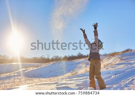 Beauty Winter Girl Blowing Snow in frosty winter Park. Outdoors. Flying Snowflakes. Sunny day. Backlit. Beauty young woman Having Fun in Winter Park #759884734