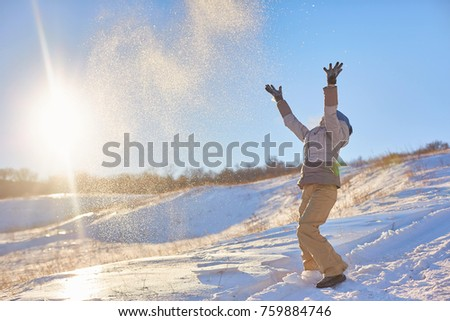 Beauty Winter Girl Blowing Snow in frosty winter Park. Outdoors. Flying Snowflakes. Sunny day. Backlit. Beauty young woman Having Fun in Winter Park #759884746