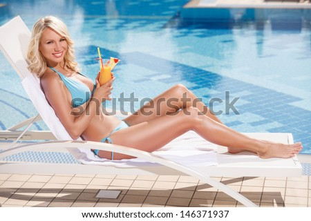 Beauty with cocktail. Attractive young women in bikini lying on the deck chair near the pool and holding a cocktail in her hand