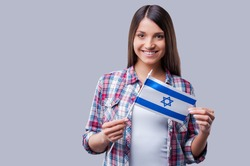 Beauty with Israeli flag. Happy young women holding flag of Israel while standing against grey background