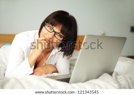 beauty with laptop lying on bed