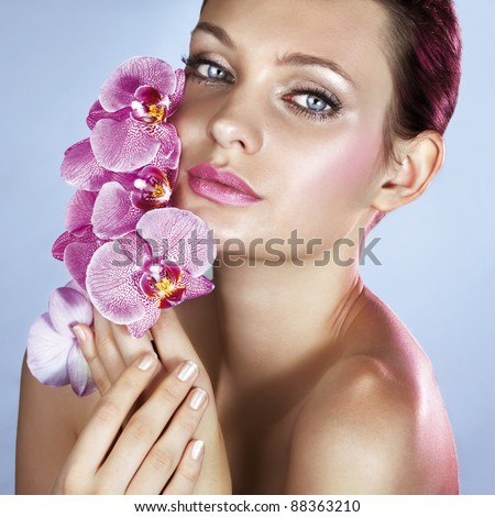 Beauty with orchids in pink light